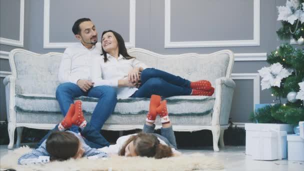 Milí rodinní příslušníci v červených ponožkách se setkávají na Nový rok. Ospalé děti leží na bílém koberci.