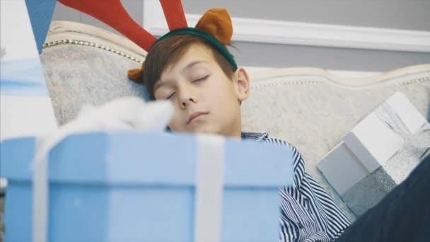 Nahaufnahme eines kleinen Jungen mit Rentiergeweih auf dem Kopf, der auf dem Sofa zwischen Weihnachtsgeschenken schläft. verschwommene Front.