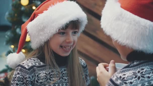 zugeschnittene Zeitlupe eines lustigen Babys mit Weihnachtsmütze, mit bösem Genie, das seinen Bruder mit Mimik ansieht, als hätte sie sich etwas Schlimmes ausgedacht.