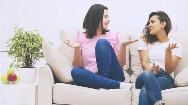 niedlichen kaukasischen und afroamerikanischen Mädchen auf dem Sofa sitzen, reden freundlich und emotional, lächeln.