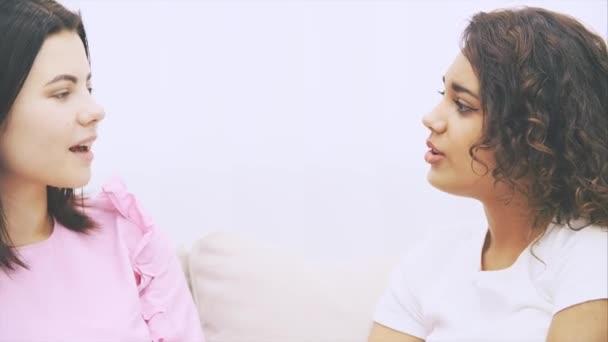 Mladá sladká dívka přátelé mluví nedbale, dívá se do kamery, pózuje, dává palce nahoru, upřímně se usmívá.