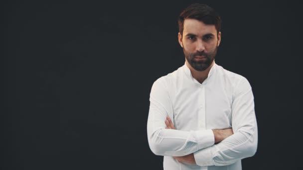 Fehér inges fiatalember, a fekete háttéren áll, pózol, összehajtogatja a kezét, magabiztosan néz a kamerába..