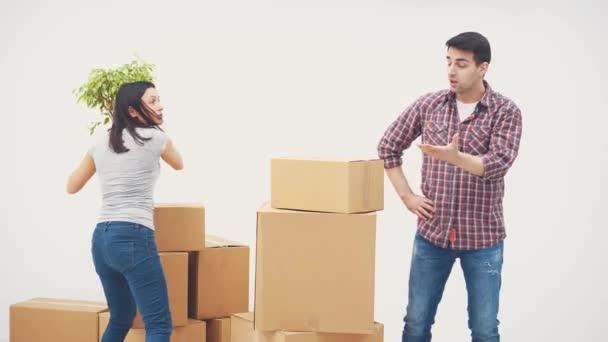 Ehepaar zieht in neue Wohnung. Sie streiten sich, weil sie nicht wissen, wo sie all die großen Pappkartons hinstellen sollen. Frau ist bereit, ihm den Blumentopf zuzuwerfen.