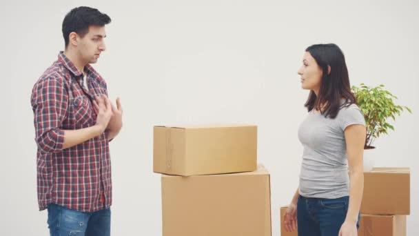 Ehepaar zieht in neue Wohnung. Sie streiten sich, weil sie nicht wissen, wo sie all die großen Kartons hinstellen sollen.