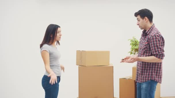 Couple is moving into new flat. They have a quarrel, because dont know where to put all those big cardboard boxes. Woman is ready to throw the box at him.