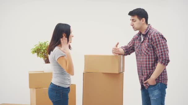 Couple is moving into new flat. They have a quarrel. Man is throwing the box at the woman.
