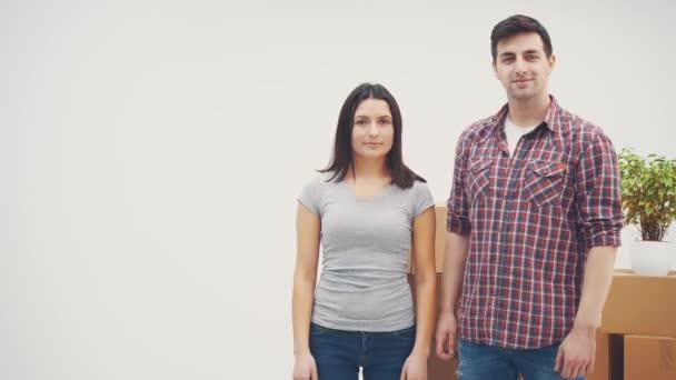 Kellemes férfi és nő áll az új lakások, mosolyogva. A férfi kulcsokat mutat, a nő feladja a hüvelykujját..
