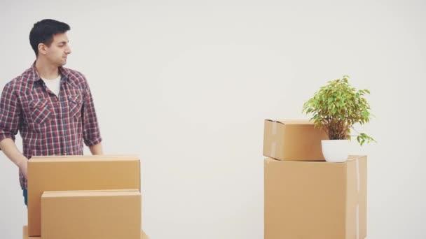 junger Mann steht in seiner neuen Wohnung, lehnt sich an den Kartonstapel, lächelt, gibt den Daumen nach oben.