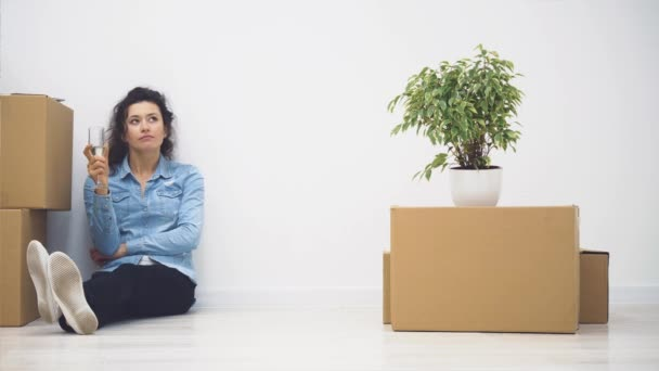 Az ifjú hölgy a padlón ül. Van egy csomó meztelen doboz és egy növény a közelében. Másold a helyet. 4k.