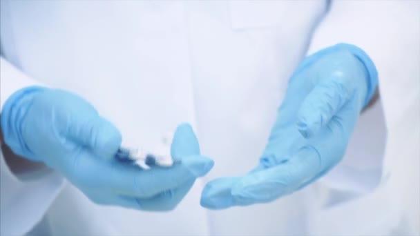 Lékařské ruce, oblečené v lékařských jednorázových rukavicích, užívající bílou pilulku z blistru.