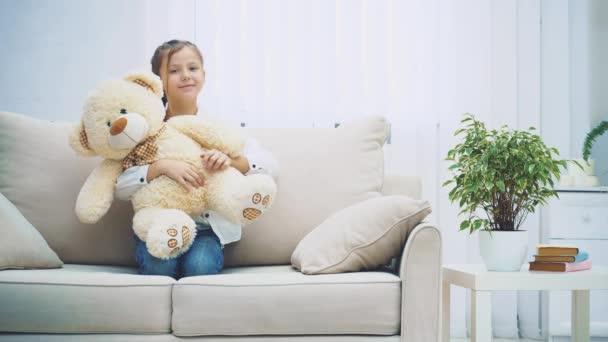 Boldog kislány ül a kanapén, ölelget egy nagy plüssmacit..