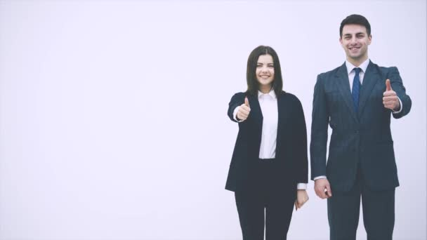 Attractive business man and woman standing side by side, giving thumbs up, smiling, looking at the copy space foe text or product on the side.