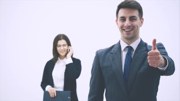 Handsome smiling businessman standing on the forefront, giving thumb up. Woman on the background is talking on the phone.