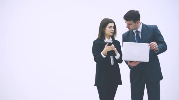 Pretty businesswoman standing with tablet in her hands, explaining something to her partner. Businessman on her side is holding laptop. They are checking data.