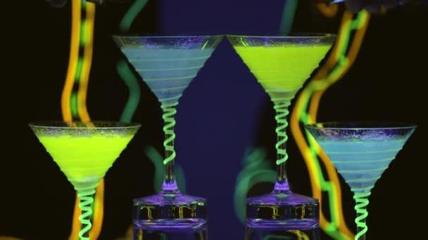 Close up Cocktailgläser, die voll mit Getränken und Trockeneis an der Bar sind. Barmann gießt Alkohol in Gläser. Fabelhafte Show. Bunte Lichter führten. Zeitlupe. 4k.