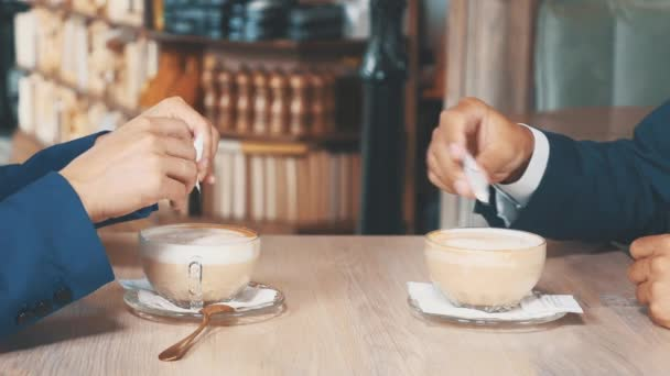 Close up coffee. Two business people have business lunch. The woman and the man in a restaurant or a coffee shop are stirring and drinking coffee. Copy space.