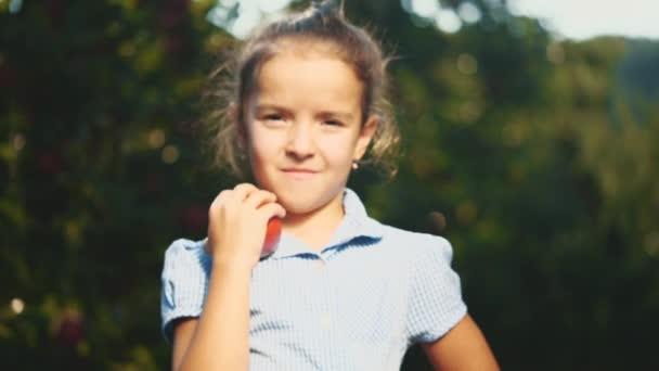 A kislány egy vörös almát kínál a szabadban. Közelről. Másold a helyet. Homályos háttér. 4k.