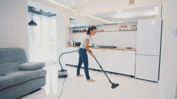 Frau staubsaugt den Küchenboden mit weißer Fliese ohne Bürste, nur Staubsaugerrohr. Kopierraum. 4k.