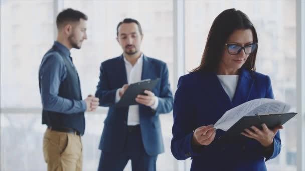 Auf dem leicht verschwommenen Hintergrund diskutieren männliche Geschäftsleute. Frau blättert an vorderster Front. Sie lächelt breit und trägt eine Brille. Kopierraum. Nahaufnahme. 4k.