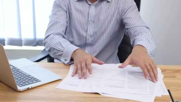 Young businessman is gathering together paperwork at desk in office. Close up. Copy space. 4K.