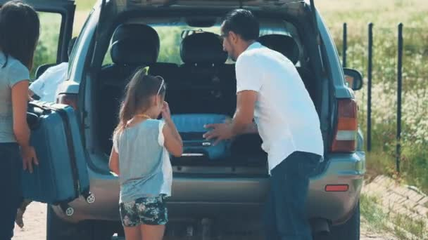 Happy family is putting suitcases into the car boot. Close up. Copy space. Hight five 4K.