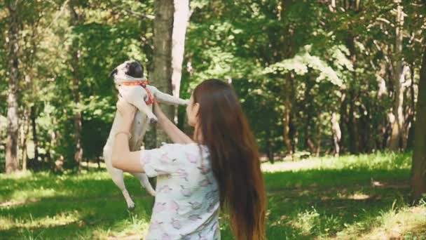 Beautiful young woman is playing with her pug dog on the park packground. Copy space. 4K.