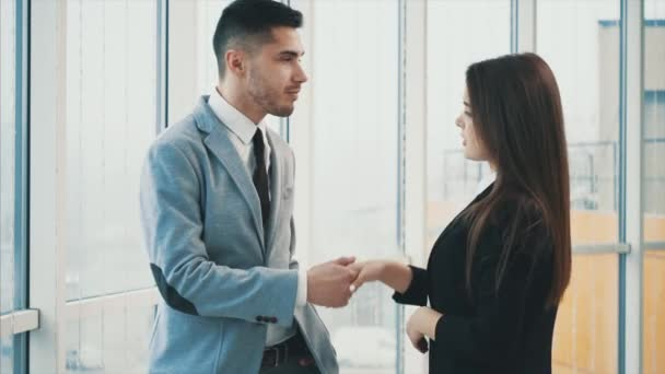 Man is looking out the panoramic window. Acquaintance of two business people in office, on the panoramic blurred background. Close up. Copy space. 4K.