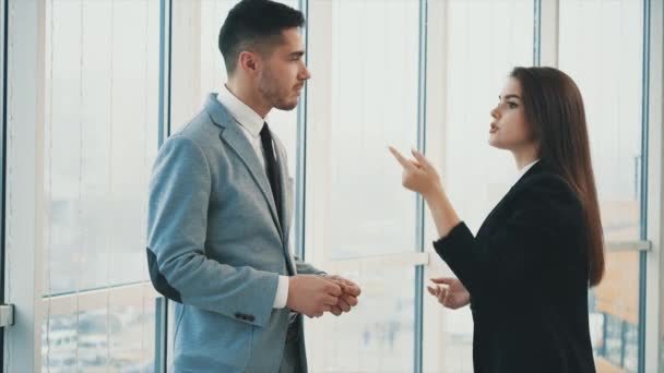 Two business people are talking in office, on the panoramaic blurred background. Close up. Copy space. 4K.