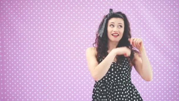 Schönes junges Mädchen mit verworrenem Haar, in schwarzen Tupfen tanzend und witzig mit den Händen winkend.
