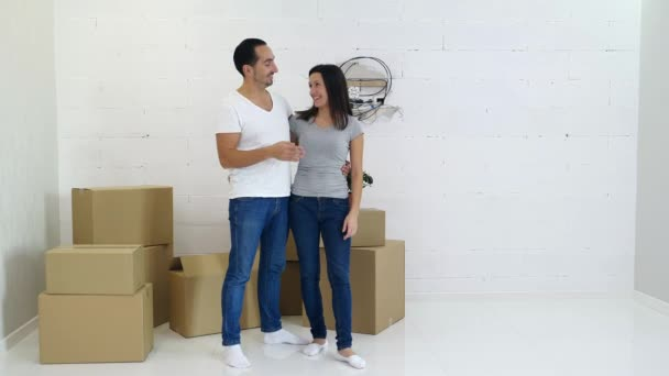 Happy couple carrying carton boxes and planning design interior of their new home.