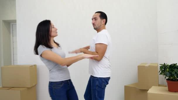 Liebevolles junges Familienpaar hat Spaß und tanzt zwischen Pappkartons in seiner neuen gemütlichen Wohnung.