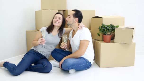 Erfolgreiches junges kaukasisches Paar feiert Umzug in seine neue Wohnung und trinkt Champagner in der Nähe von Schachtelstapeln.