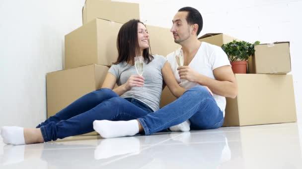 Begeistertes junges Paar sitzt in einer neuen Wohnung neben Pappkartons auf dem Boden, diskutiert über den Grundriss des Hauses und trinkt Sekt.