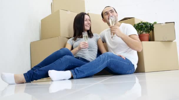 Successful young caucasian pair celebrating move to their new flat drinking champagne near stack of boxes.
