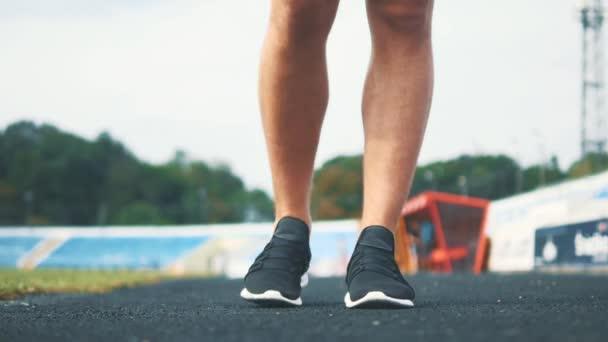 Bělošský muž běžec zahřívá tím, že protahuje svaly šlach nohou před tréninkem na městském stadionu. Zavřít. Rozumím. 4K.