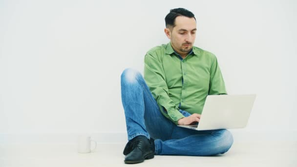 Izolovaný seriózní mladý muž sedící na podlaze s laptopem na koleni a hledající na internetu se soustředěným výrazem ve tváři.