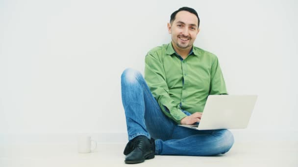Young man sitting on the floor with laptop on his knee and a white cup on his side, watching something funny in his laptop, dancing, smiling at the camera.