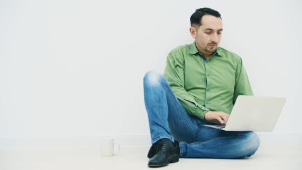 Soustředěný mladý muž sedící na podlaze s laptopem na koleni, psal, hledal na internetu, pil kávu.