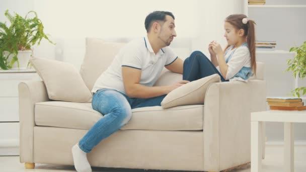 4k zpomalení video, kde roztomilé dítě dcera na pohovce s tátou konverzace.