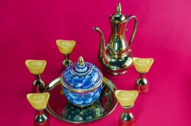 Gold ingot Gold jug Tea glass benjarong  on red background.