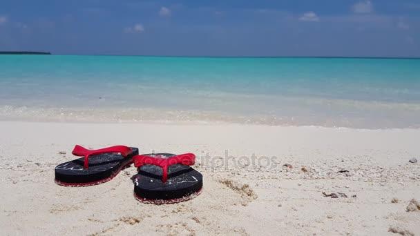 v01765 Maldives beautiful beach background white sandy tropical paradise island with blue sky sea water ocean 4k black red flip flops