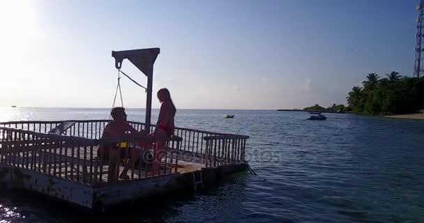 v03830 létající dron pohled Maledivy pláž s bílým pískem 2 osoby mladý pár muž žena uvolňující na slunečné tropické paradise island s aqua blue sky moře vody oceánu 4k plovoucí Ponton mola