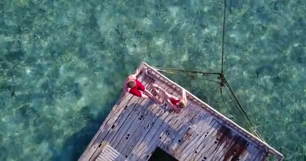 v03825 Aerial flying drone view of Maldives white sandy beach 2 people young couple man woman relaxing on sunny tropical paradise island with aqua blue sky sea water ocean 4k floating pontoon jetty