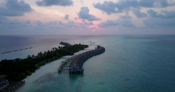 v03577 Aerial flying drone view of Maldives white sandy beach on sunny tropical paradise island with aqua blue sky sea water ocean 4k luxury 5 star resort hotel water bungalow hut relaxing holiday