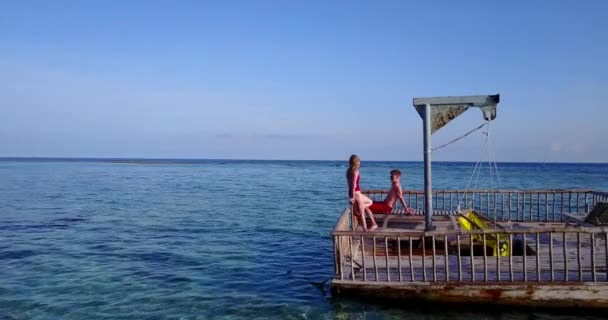 v03833 Aerial flying drone view of Maldives white sandy beach 2 people young couple man woman relaxing on sunny tropical paradise island with aqua blue sky sea water ocean 4k floating pontoon jetty