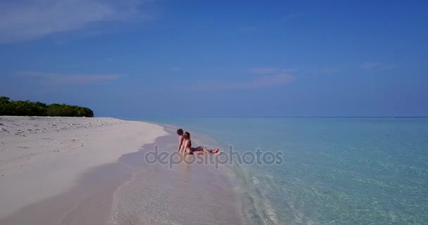 v03871 Aerial flying drone view of Maldives white sandy beach 2 people young couple man woman romantic love on sunny tropical paradise island with aqua blue sky sea water ocean 4k