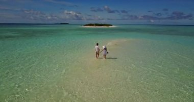 V03906 Aerial flying drone view of Maldives white sandy beach 2 people young couple man woman romantic love on sunny tropical paradise island with aqua blue sky sea water ocean 4k