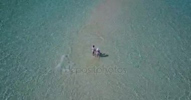 V03924 Aerial flying drone view of Maldives white sandy beach 2 people young couple man woman romantic love on sunny tropical paradise island with aqua blue sky sea water ocean 4k