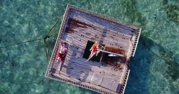 v03821 Aerial flying drone view of Maldives white sandy beach 2 people young couple man woman relaxing on sunny tropical paradise island with aqua blue sky sea water ocean 4k floating pontoon jetty
