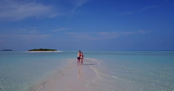 v04031 Aerial flying drone view of Maldives white sandy beach 2 people young couple man woman romantic love on sunny tropical paradise island with aqua blue sky sea water ocean 4k